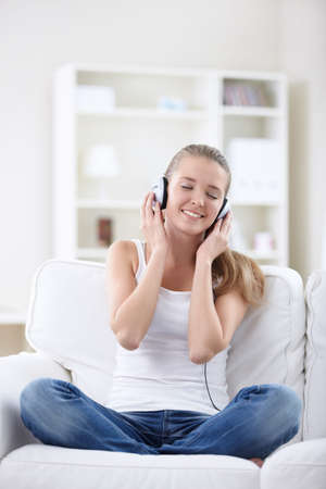 A young girl listens to music on headphones photo