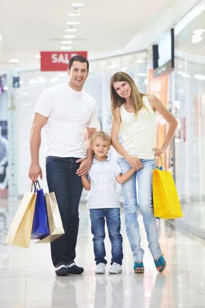 ni�os de compras: Familia joven con sus bolsas en la tienda  Foto de archivo