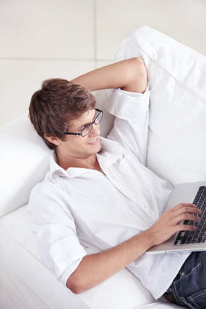 A young man on the couch with a laptop works photo