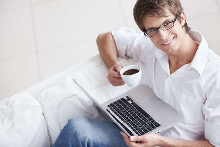 adult only: A young man with a cup and laptop