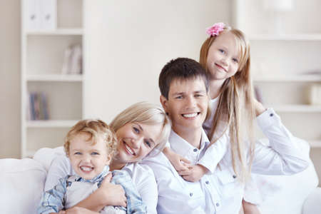 Young happy family with two children at home photo