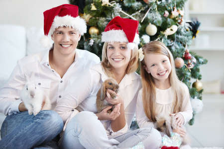 Happy family in Christmas caps with the rabbits on the background of trees photo