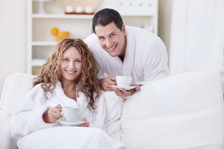 A happy young couple in dressing gowns at home photo