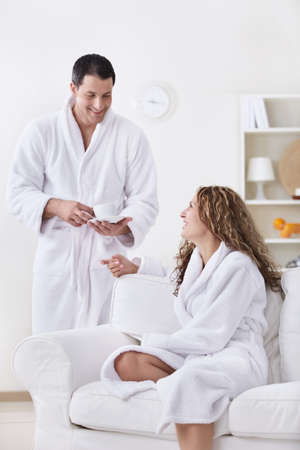 dressing gowns: Laughing couple in dressing gowns at home