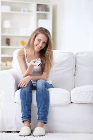 switches: A pretty girl on the couch at home switches TV channels Stock Photo