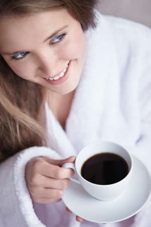 A young girl holding a cup of coffee close up photo