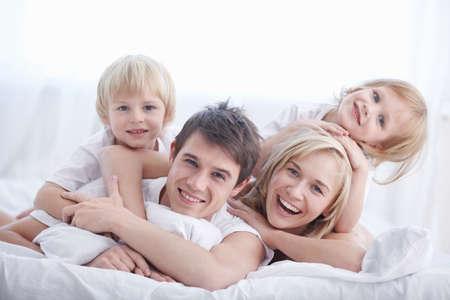 lit: Une famille heureuse sur lit de couleur blanche dans la chambre � coucher  Banque d'images