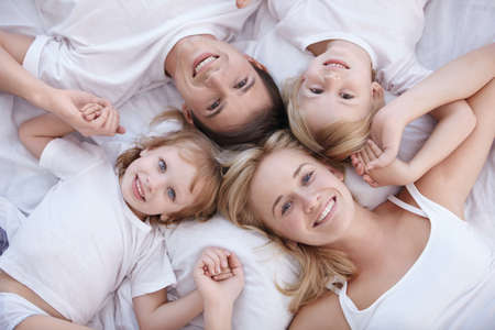 Smiling family lie on a white bed photo