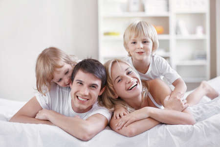 boy bedroom: Smiling parents with children at home Stock Photo
