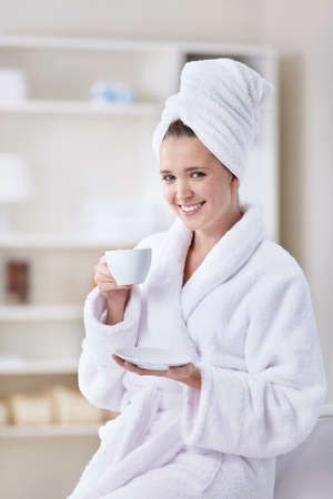 woman bathrobe: A beautiful young girl in a bathrobe and a towel with a cup of coffee