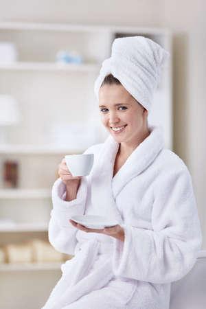 bathrobes: Una hermosa joven en un albornoz y una toalla con una taza de caf�  Foto de archivo