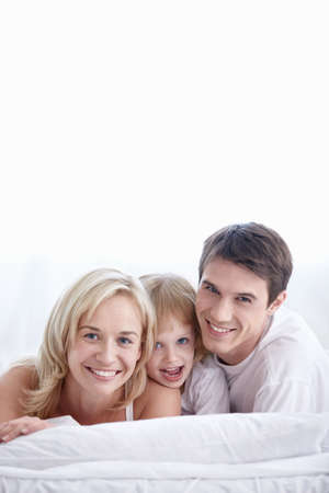 Attractive family with young daughter in the bedroom