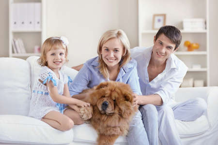 family on couch: Happy family with dog at home Stock Photo