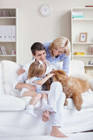 Smiling family pat the dog at home photo