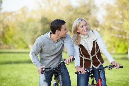 Young happy couple in the park on bicycles photo