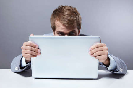 leans: An attractive man leans out of the laptop Stock Photo