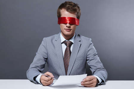 closed ribbon: A young businessman signs a contract with a blindfold