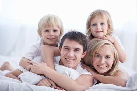 girl bedroom: A family with two children on a bed in the bedroom Stock Photo