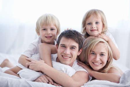 mujer en la cama: Una familia con dos hijos en una cama en el dormitorio