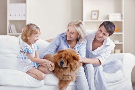 man couch: Young family with a dog at home