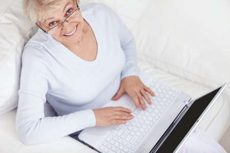 An attractive middle-aged woman with a laptop on a white sofa photo