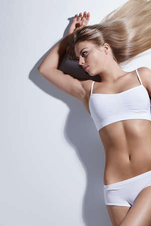 Attractive athletic girl lying on a white background