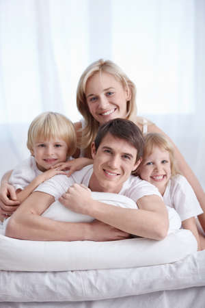 Attractive family with children in the bedroom photo