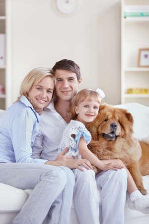 Familia feliz con el perro en casa
