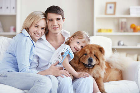 animal family: Embracing family with a child and a dog Stock Photo