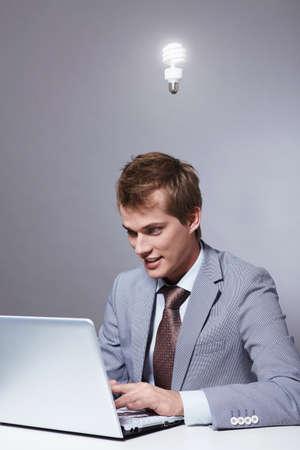 Burning light bulb over his head working businessman photo