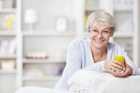 one senior adult woman: Mujer atractiva madura con un vaso de jugo