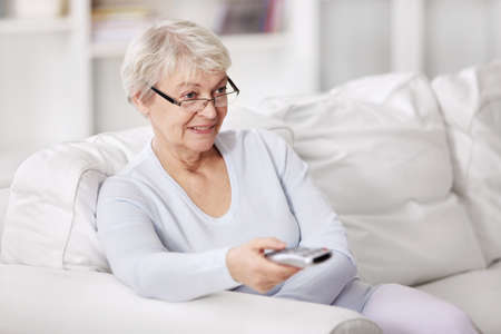 switches: An attractive older woman switches TV channels
