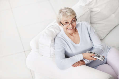 only mature women: Mature attractive woman with a remote control from a TV on a white sofa Stock Photo
