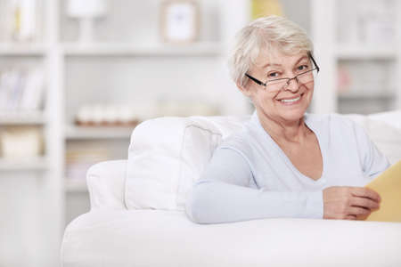 Mature attractive woman with a book on the couch photo