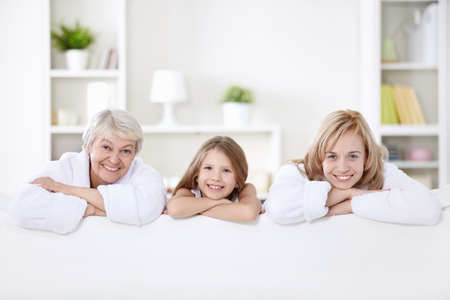 woman bathrobe: Three generations of women on the couch at home