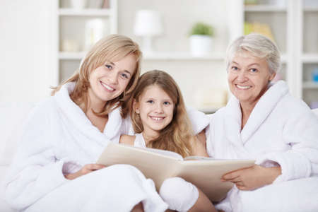 3 generation: Attractive family home with a book Stock Photo