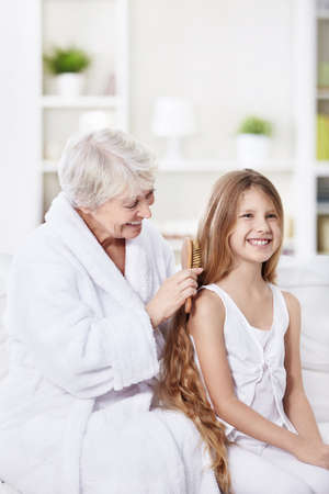 Grandmother granddaughter combs her hair at home
