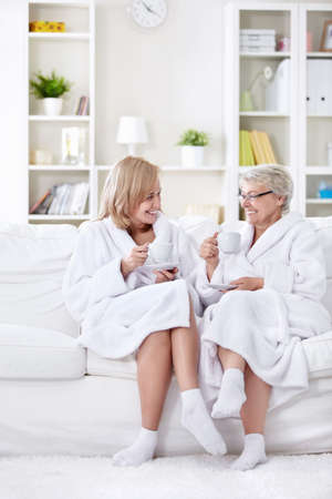 Mom with grown-up daughter tea on the couch photo