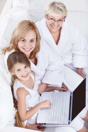 Families with a laptop on a white sofa Stock Photo - 8417404