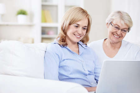 Smiling mother and daughter looking at laptop Stock Photo - 8417397