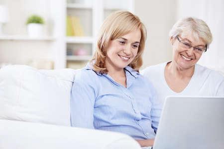 senior ordinateur: Sourire m�re et fille regardant portable Banque d'images