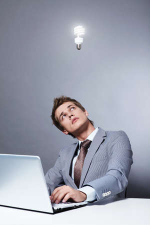 Young businessman in a suit looks at a burning light bulb photo