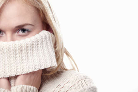 sueteres: Chica atractiva cubre su rostro con un su�ter sobre un fondo blanco Foto de archivo
