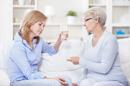 Mature woman gives a young woman pills photo
