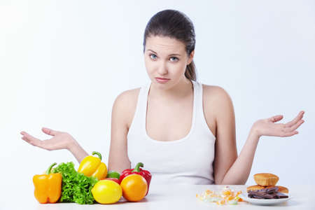 Doubting the girl with a healthy diet and sweet on a white background Stock Photo - 8645345