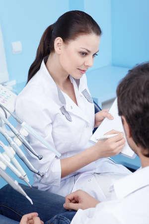 hombre escribiendo: Conversaciones de dentista atractivo a los pacientes Foto de archivo