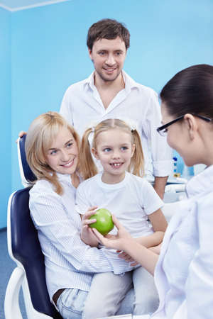 Dentist gives Apple a child in the dental office Stock Photo - 8645381