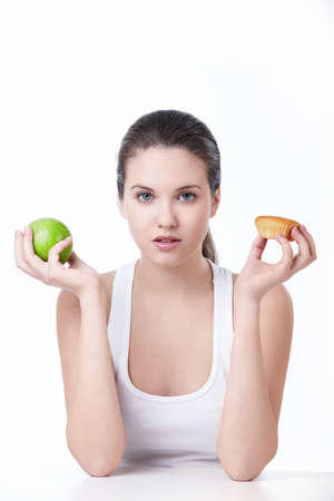 Young beautiful girl holding a green Apple and cake on a white background photo