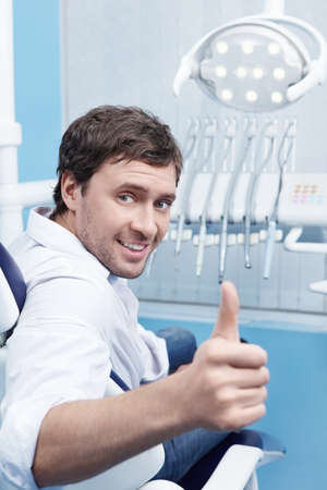dental tools: A young man in a dental chair shows thumbs up