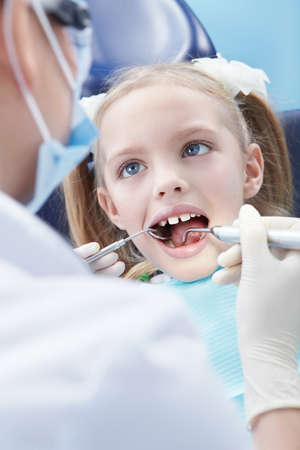 Child examines the dentist in the clinic photo